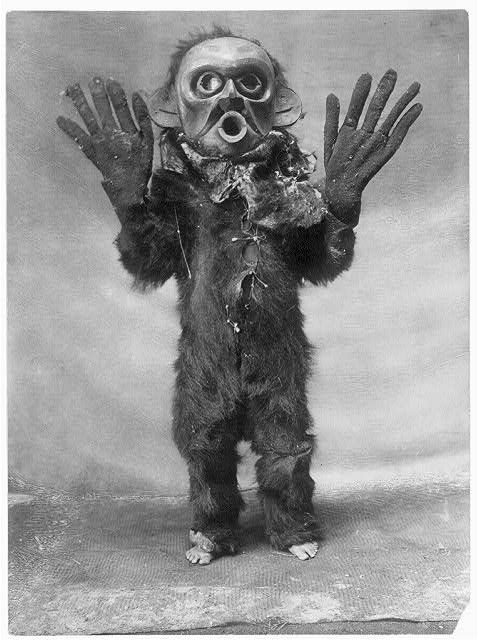 "A Koskimo wearing full-body fur garment, oversized gloves and mask of Hami (""dangerous thing"") during the numhlim ceremony. 1910's"