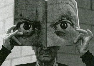 Charles Eames posing with a mask of Picasso's eyes